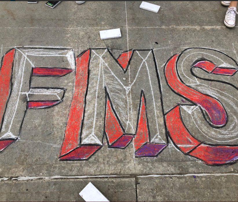 Letters FMS drawn in sidewalk chalk