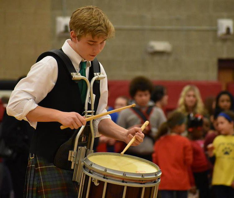 A GHS student plays a drum, in a Scottish kilt, at the 2018 Cultural Fair