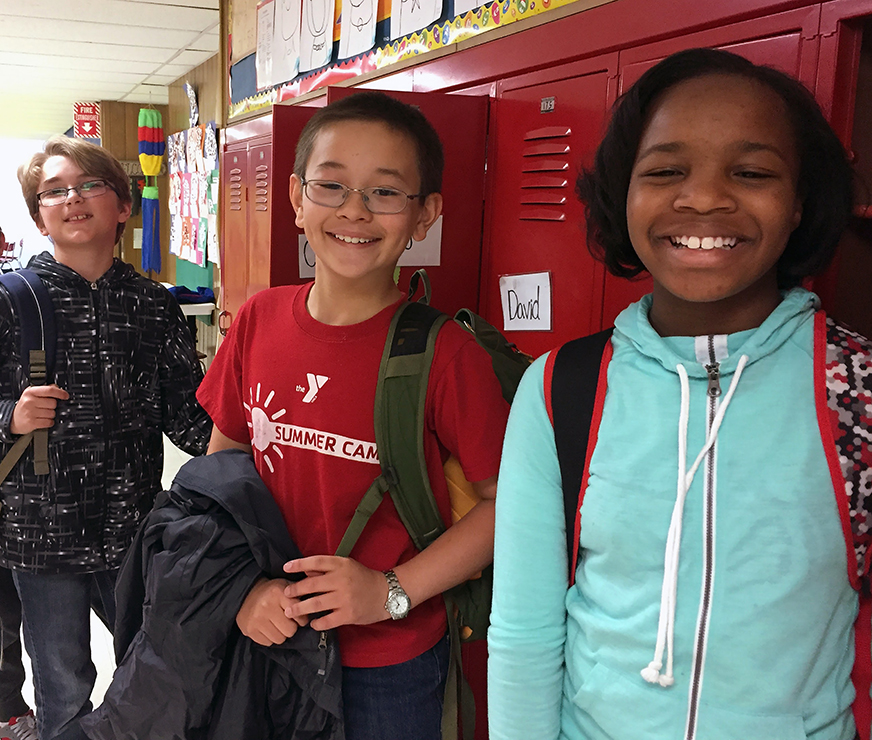 Three students stand by their lockers for a smile break