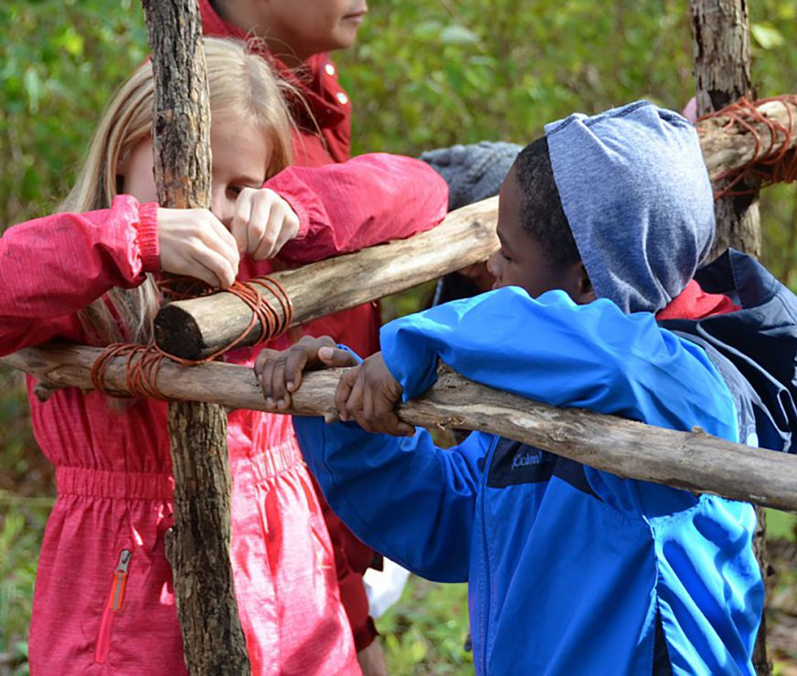 Two students work together at the annual Longhouse building