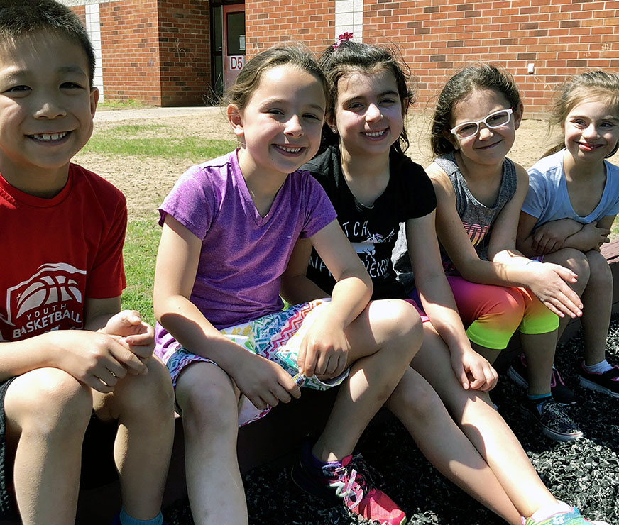 Five students sit outside during recess for a smile break