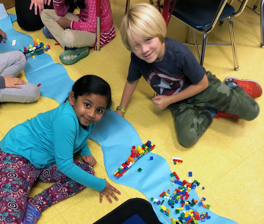 Two student build a Lego bridge over a paper river