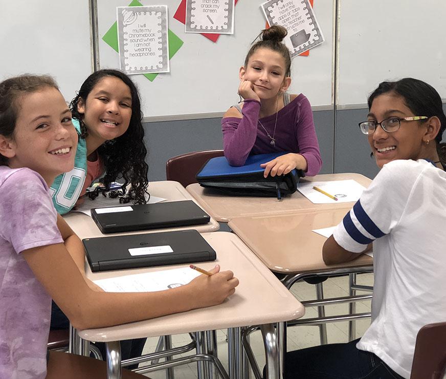 Four girls smile at their desks
