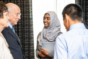 GHS student Tasnim speaks with one of the researchers being honored