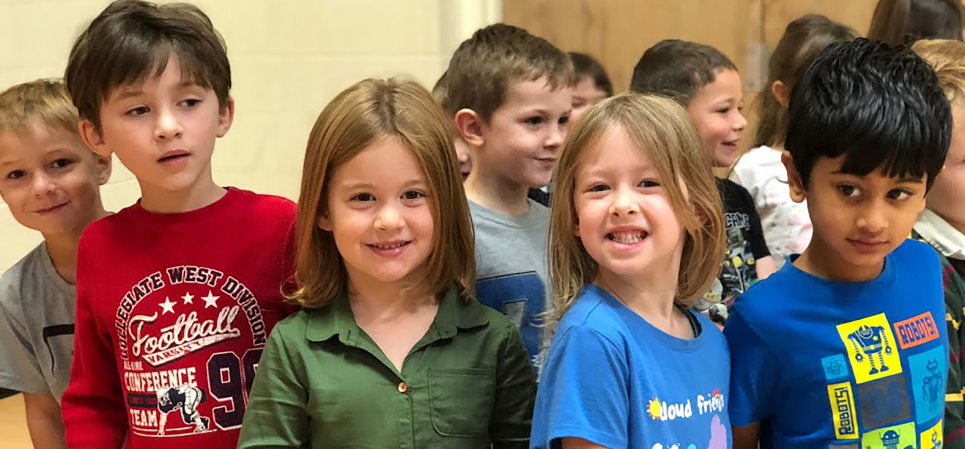 Four kindergartners smile for the camera during gym class