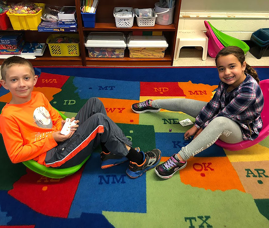 Two students take a break from reading on the ground, to smile