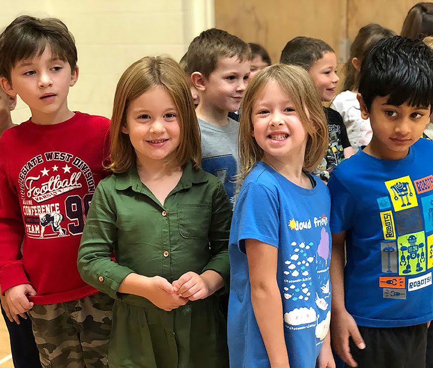 Group of four students wait in line for gym class with a smile