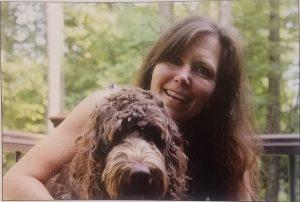LES social worker Catherine Ricchetti hugs her service dog, Copeland