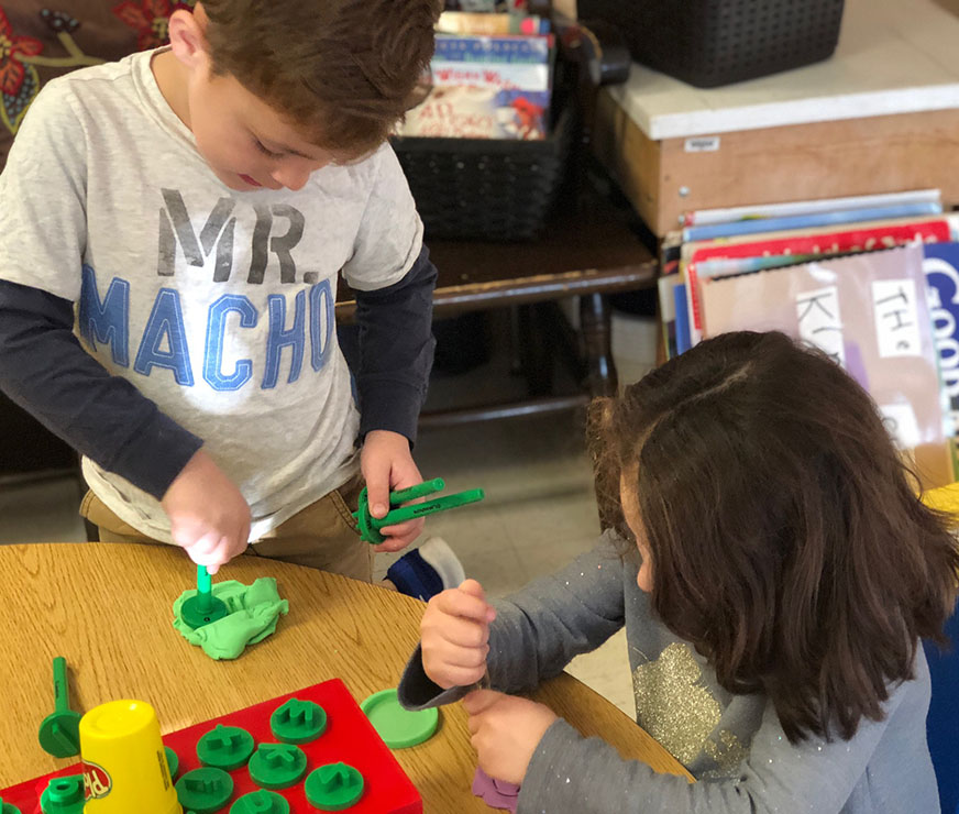 Two students mold playdough