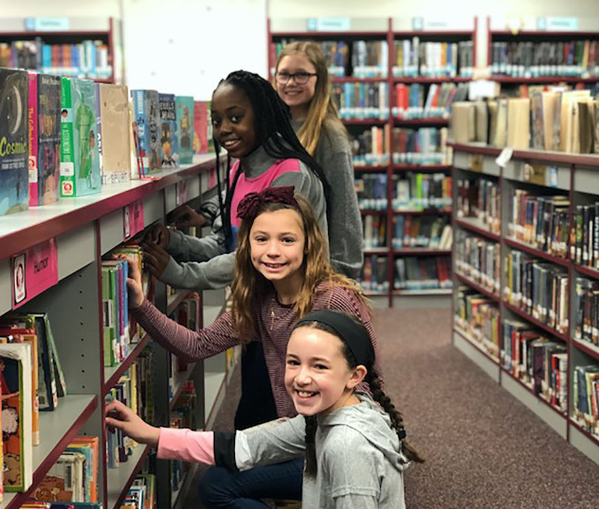 Four girl in a line stop from perusing a bookshelf to smile for the camera