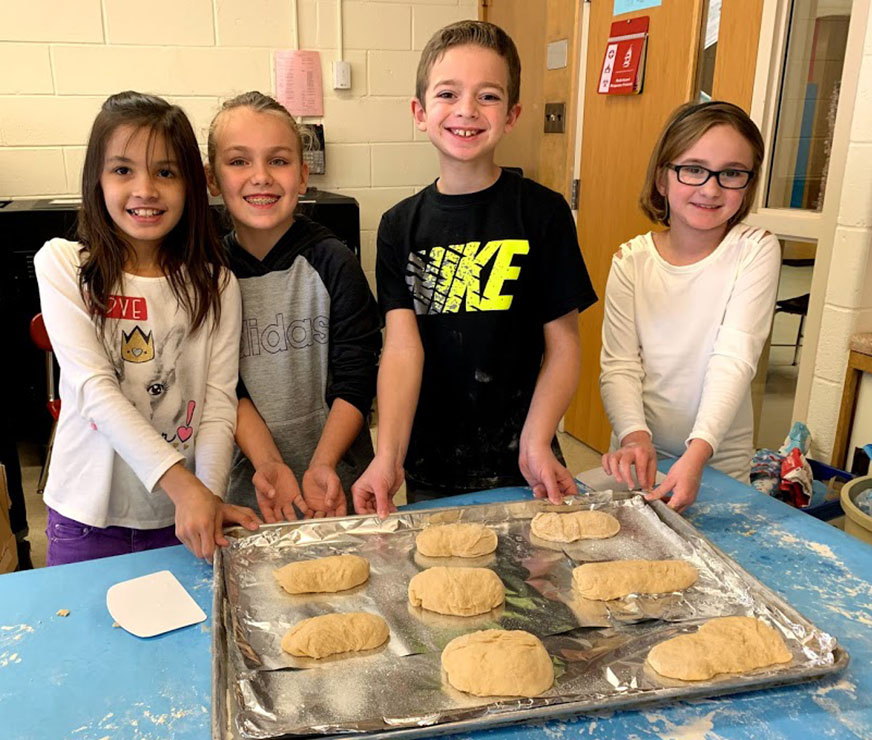 Four AES students pose by bread dough they're about to bake