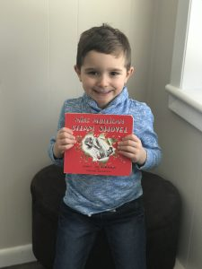 Young boy holds up Mike Mulligan book