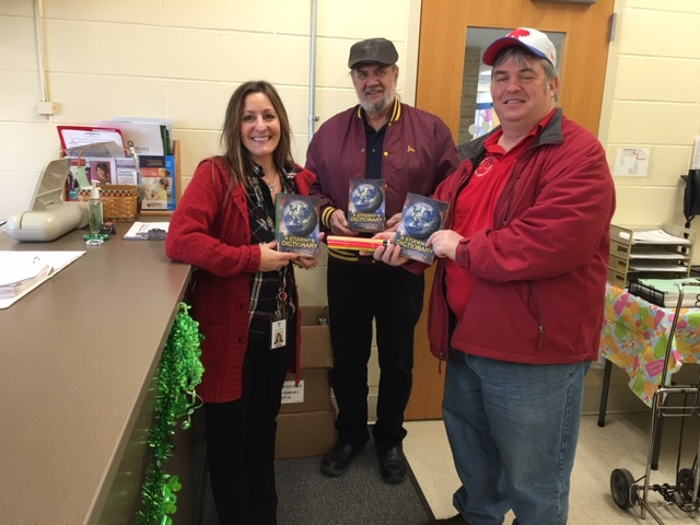 Mary Jo, school secretary, poses with two members of the Elks Club members and their donated dictionaries and pencils