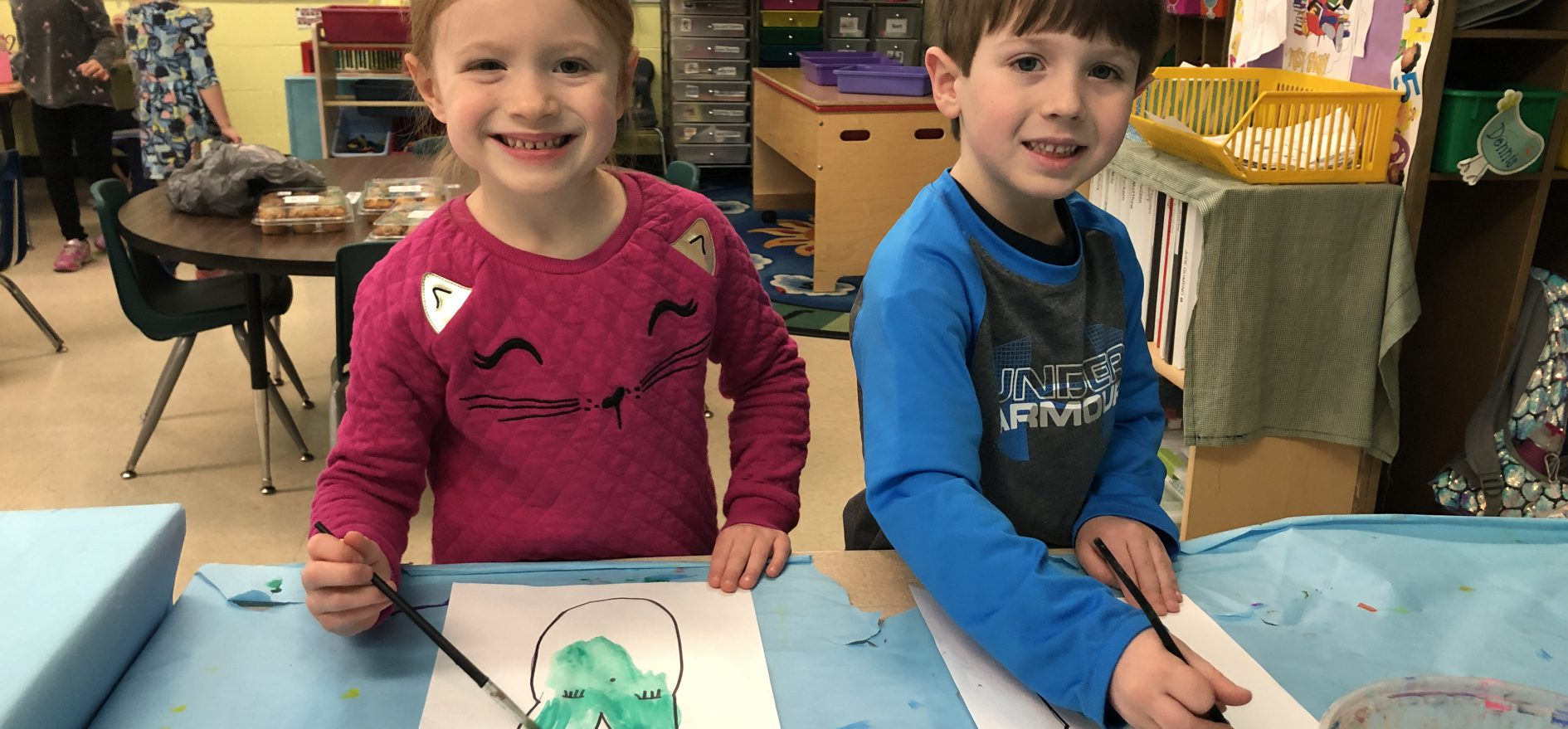 Two LES second graders smile while using watercolors to paint a paper bunny