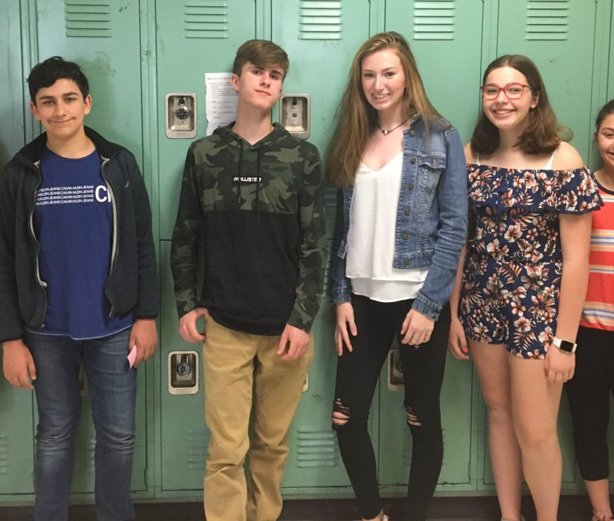 Seven students pose by lockers for a smile