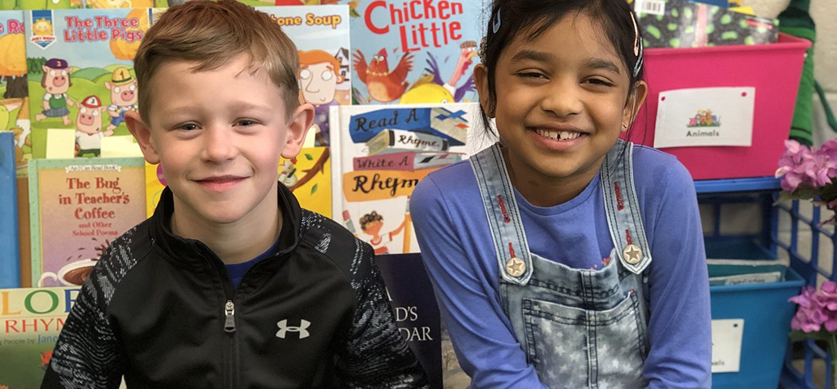 Two students smile for the camera