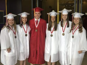 Six grads from the class of 2019 smile for a photo