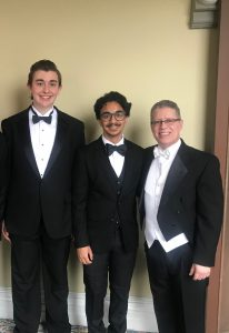Two students pose with conductor