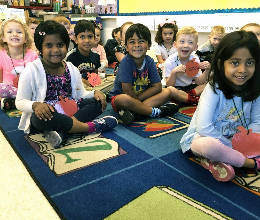 Westmere Elementary students smiling while sitting on reading rug