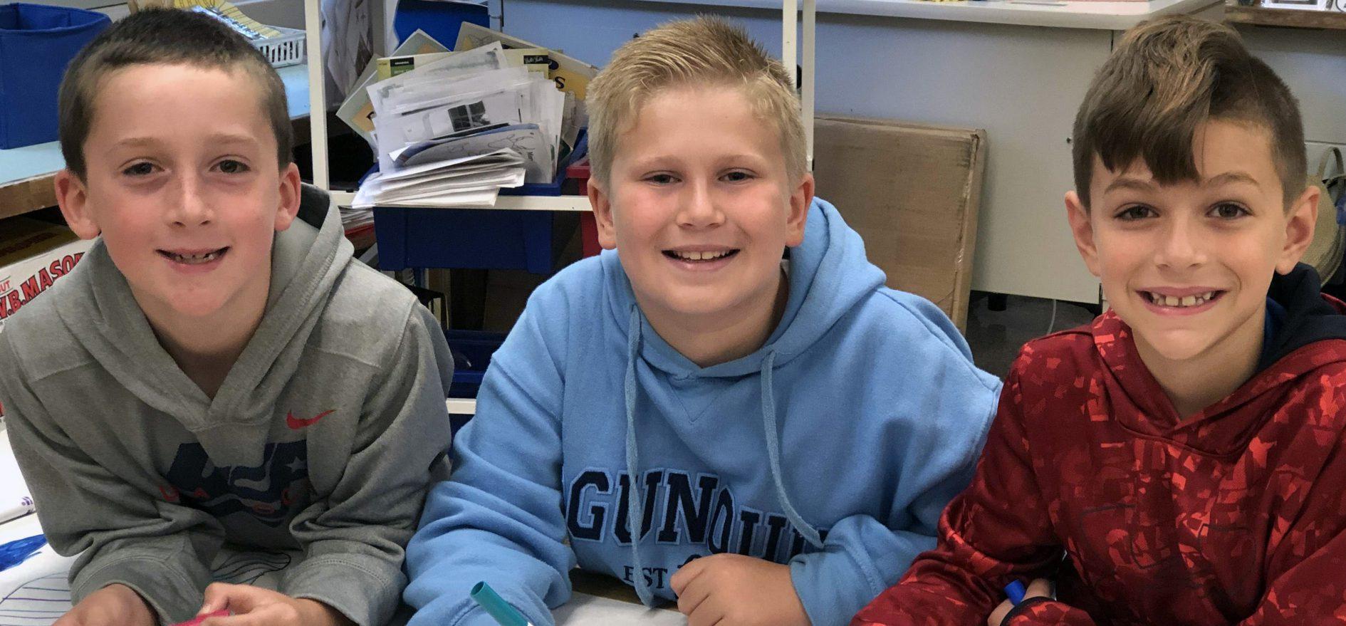 Three second grade boys smile for a photo