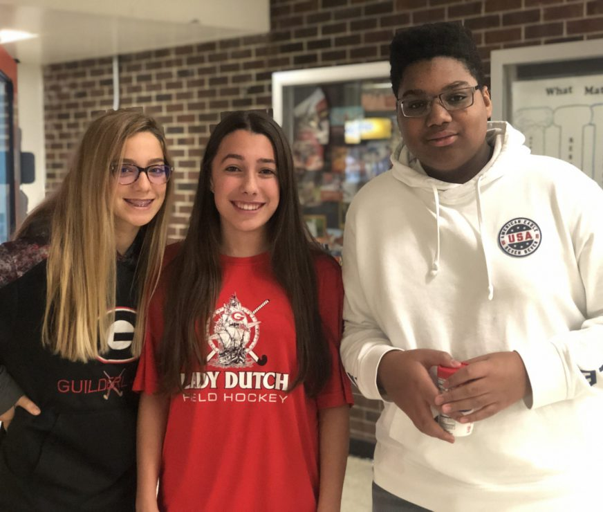 Three FMS students, two girls and a boy, stop for a smile