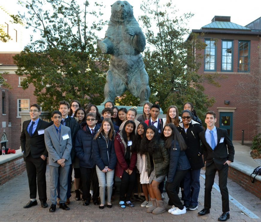 A group of GHS Model UN student stand in front of Brown University bear statue for a photo