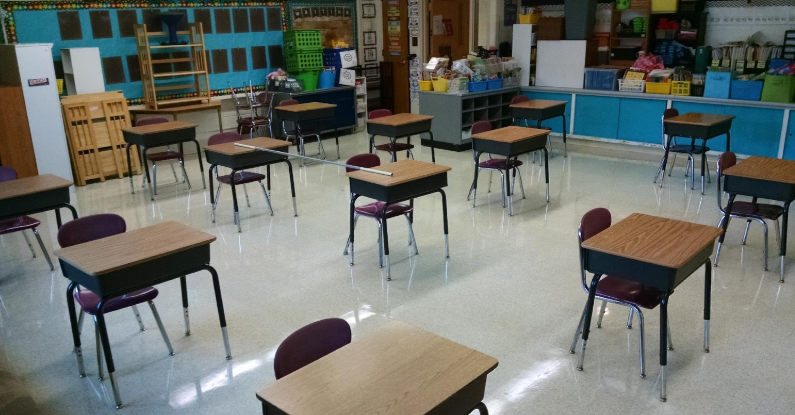 Classroom set up with individual desks at least six feet apart