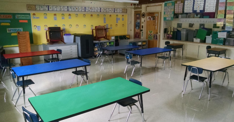 Classroom set up with tables, chairs on each end of the tables facing each other.