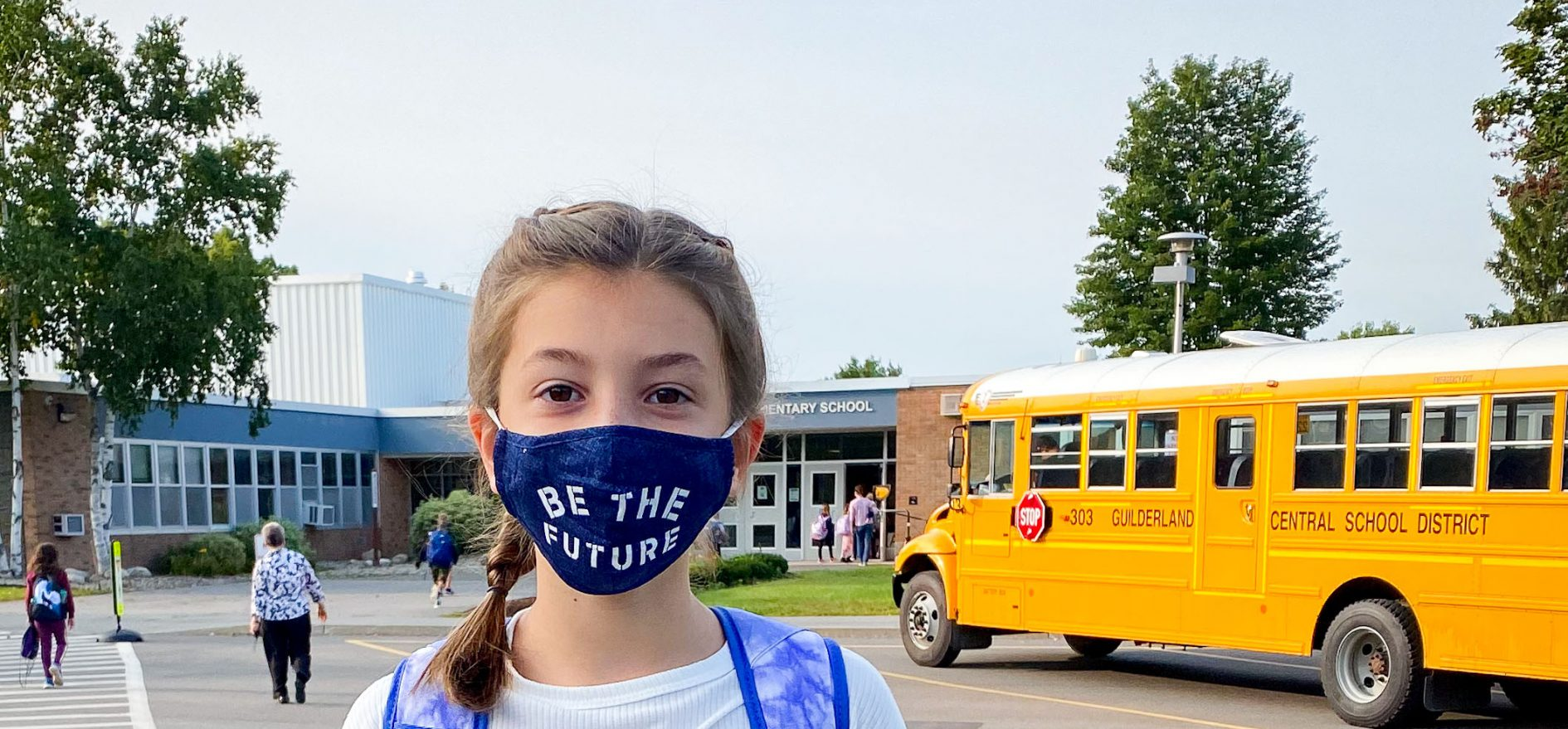 "Student in front of school wearing a mask saying ""Be the future"""