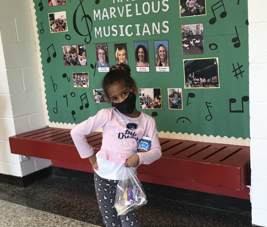 Small LES student strikes a pose in front of sign, wearing a mask and holding lunch
