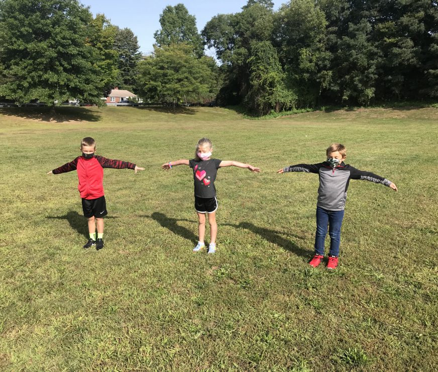 PBES Students outside showing an arms length away is a healthy distance to help prevent COVID-19