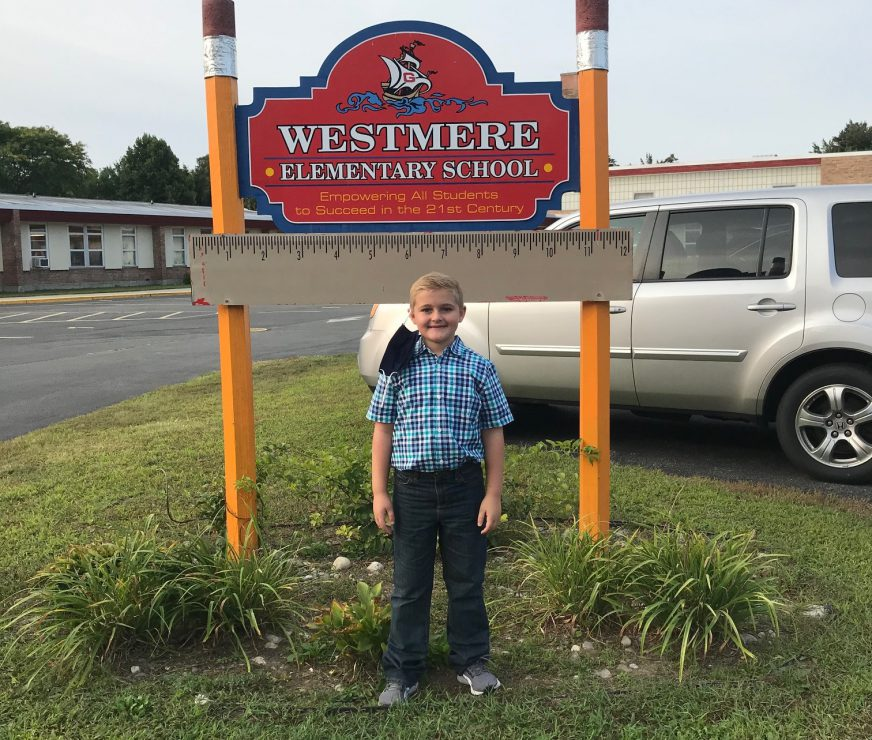 student standing in front of Westmere sign