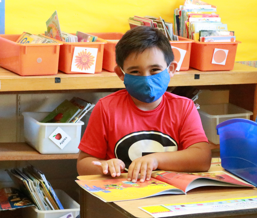 You can see the smile behind the mask of this GES student at their desk smiling