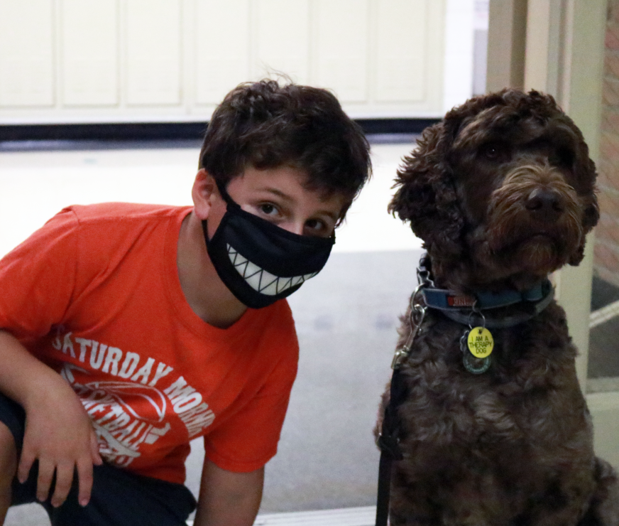 LES student (with smiling mask) crouched with the LES Therapy dog