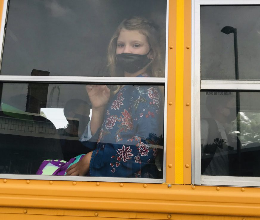 Student on the bus peering out the window in anticipation of the first day of school