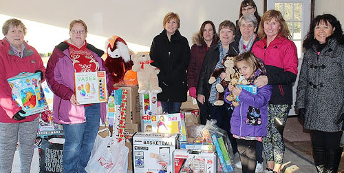 members of the GCSD TA's Association standing in front of many donations for the annual toy drive. The donations are delivered unwrapped to the organization and then the gifts are delivered to local children in need.