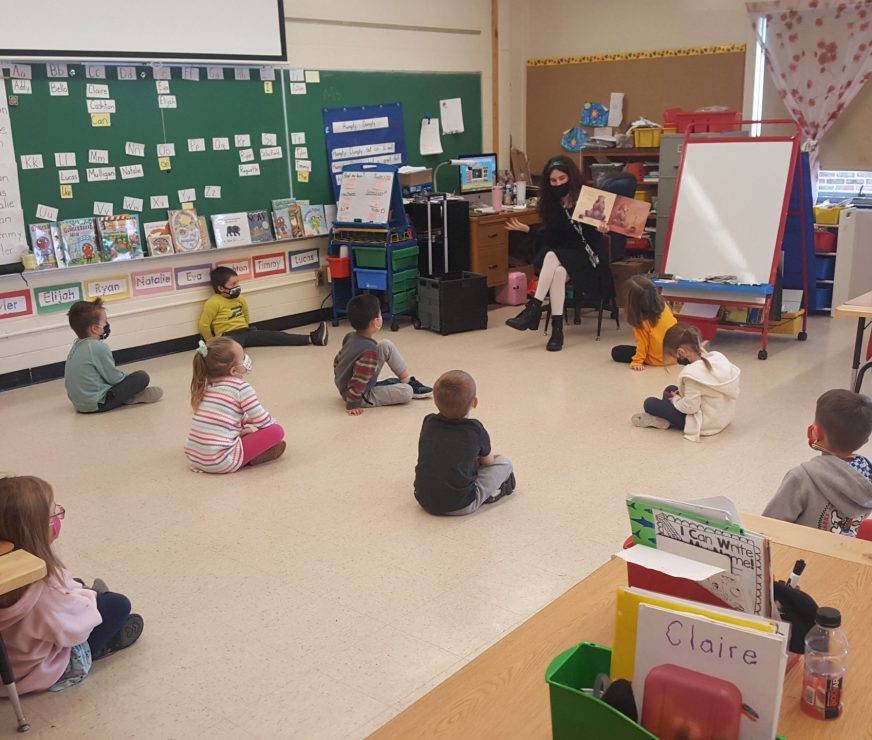 AES students in a classroom sitting socially distanced apart looking up at a teacher reading a book