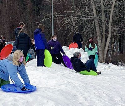 A group of students outside in the snow with sleds and Principal Laster sliding on a sled
