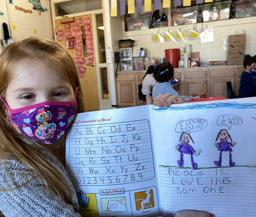"""Student wearing a mask, holding up a composition notebook with artwork of two people. One person has a comment bubble that reads, """"I Love You."""" The other person's comment bubble reads, """"I Love you to."""" A sentence below reads, """"Peace is LOVE ing som one."""""""