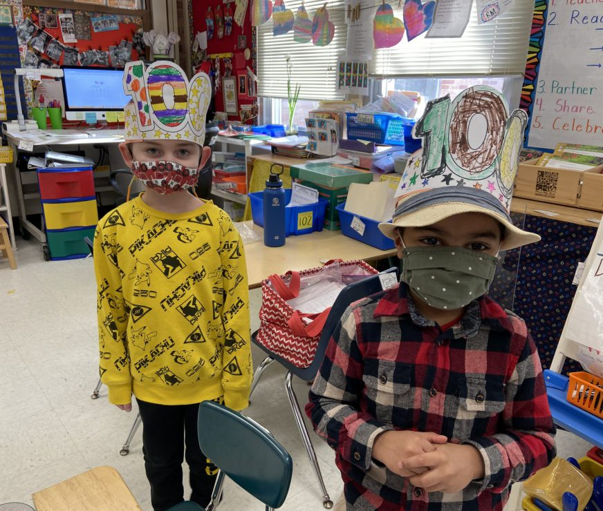 Two masked GES students standing next to each other wearing hats that they colored 100. The background is a colorful classroom with class projects and bulletins.