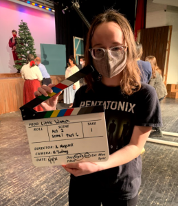 masked student standing on a stage holding a clapperboard for filming for Little Women. Costumed cast in the background.