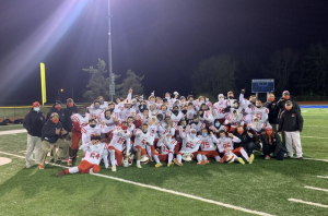 Guilderland Central School District's Varsity Football team dressed in white and red uniforms pose in a group with coaches under the night lights on their home field.
