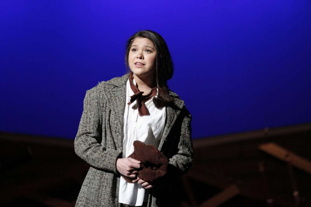 Guilderland High School student Nicaya-Isabella Rios, dressed in white blouse, brown scarf and oversized tweed jacket, performs onstage. The stage is lit in a bright blue.