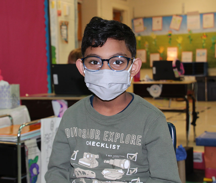 Altamont Elementary student with dark hair and glasses wearing a mask sitting in classroom