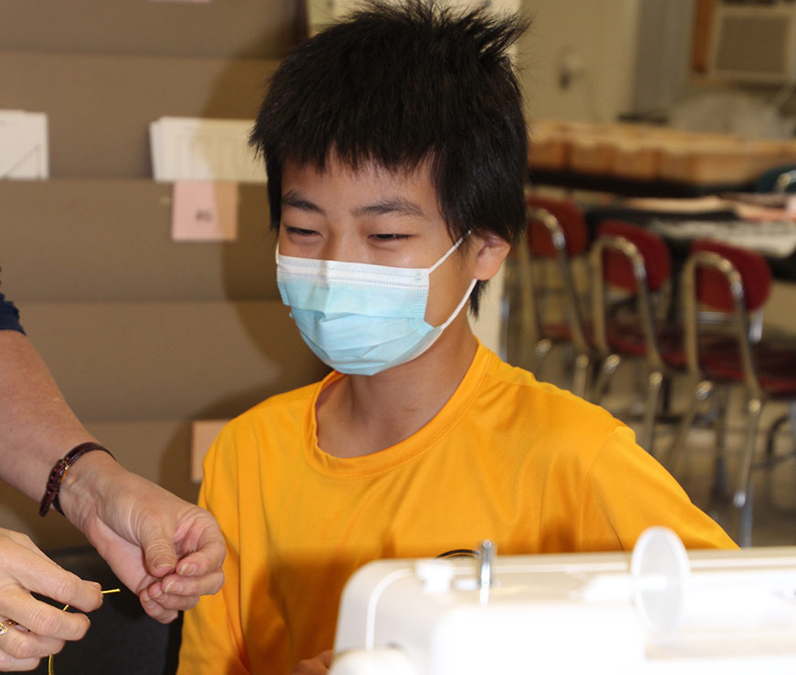 Farnsworth Middle School student wearing a mask in a sewing classroom being shown how to thread a needle