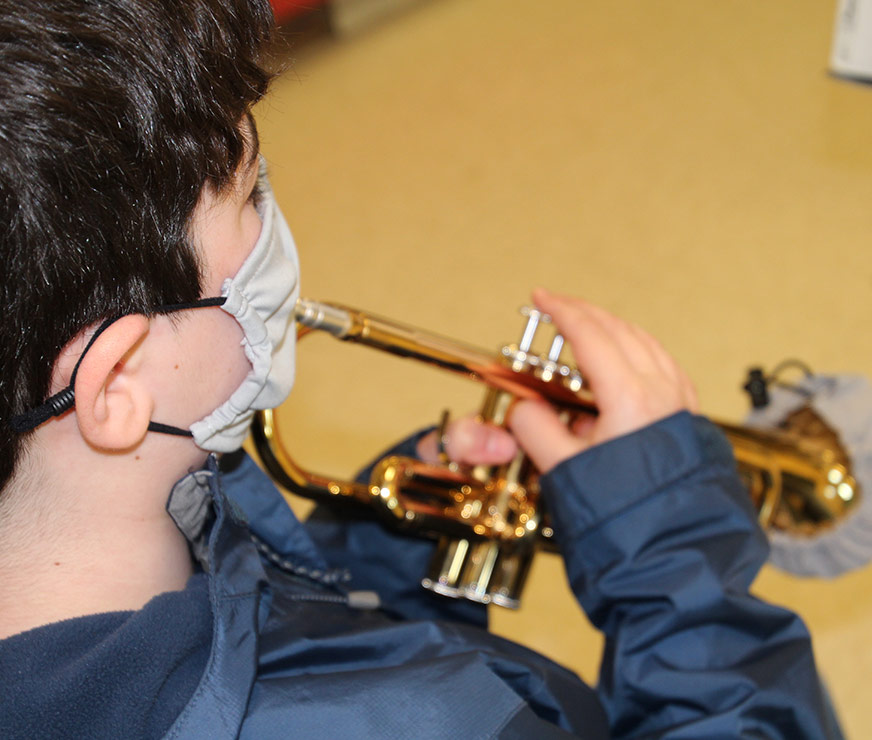 Farnsworth Middle School student playinf trumpet with a mask on and a covering on the end of the trumpet.