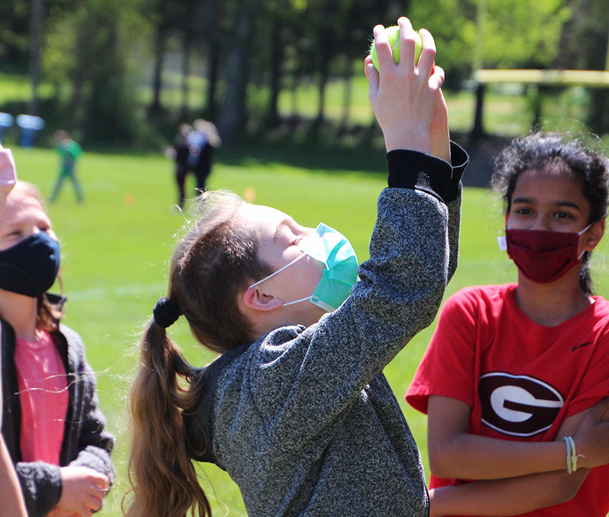 Farnsworth Middle School student outside wearing mask arms over head catching tennis ball