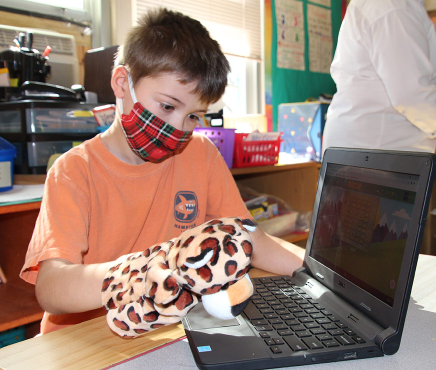 Guilderland Elementary student wearing a plaid mask sitting at a laptop with a handpuppet of a leopard
