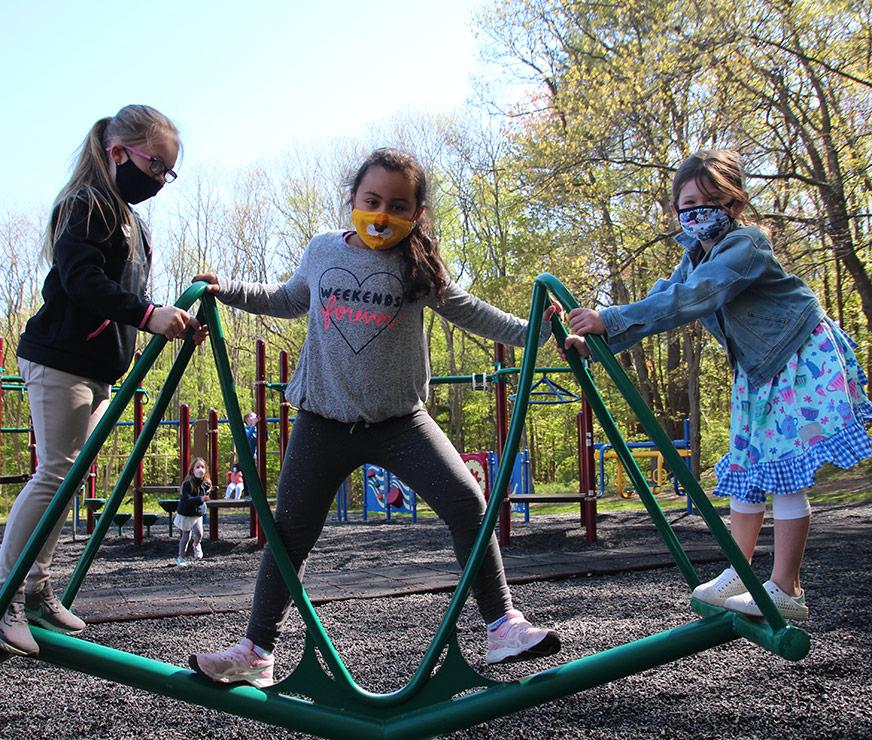 Guilderland Elementary three students shar a piece of playground equipment wearing masks