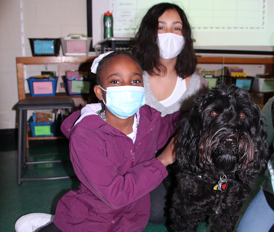 Guilderland Elementary student wearing mask sitting on floor with service dog.